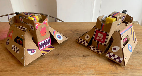 Photo of two cardboard robots with flippers, covered with decorative stickers featuring checker patterns, roundels, sharks eyes and teeth and hazard warning markings.