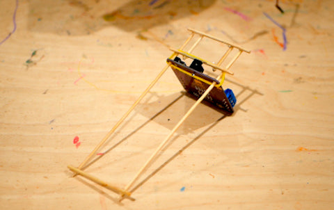 Image of a wooden structure, made from kebab sticks, around a circuit board.