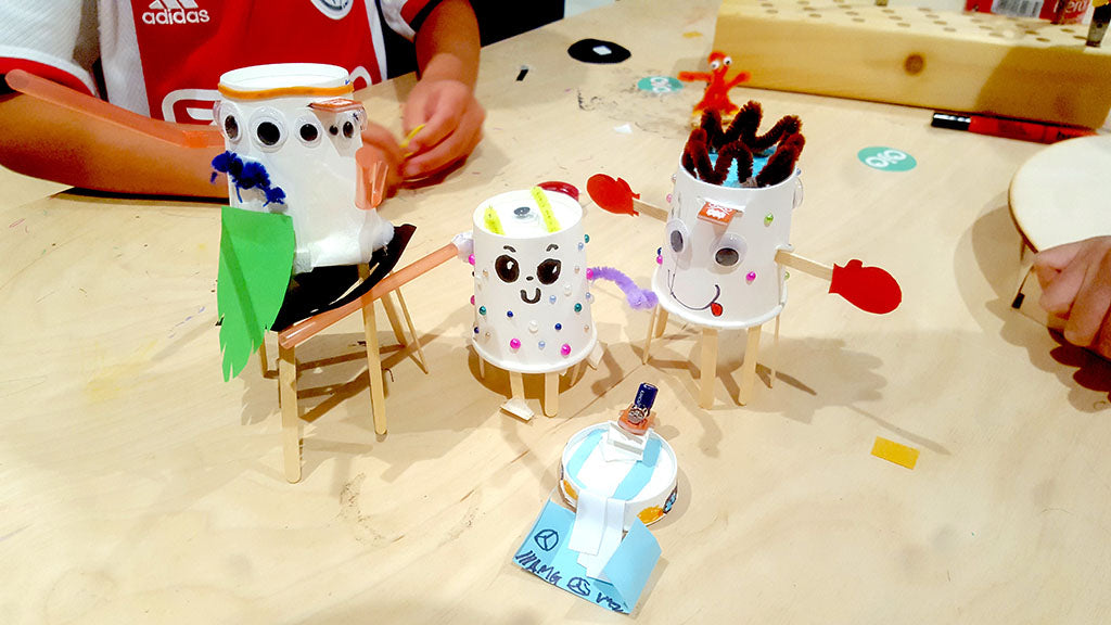 Image of three paper cup robots and one cup lid robot decorated with recyclable materials