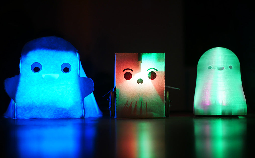 Photo of three small cartoon-style ghosts all internally illuminated with coloured light, one made of felt, one made of paper and one made from frosted plastic