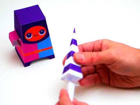 Photo of the handle being stuck onto a paper lance, with a brightly coloured paper knight in the background