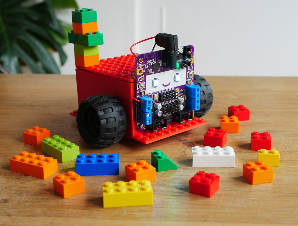 Photo of Smartibot with red body with LEGO type bobbles on top, surrounded by lego bricks.