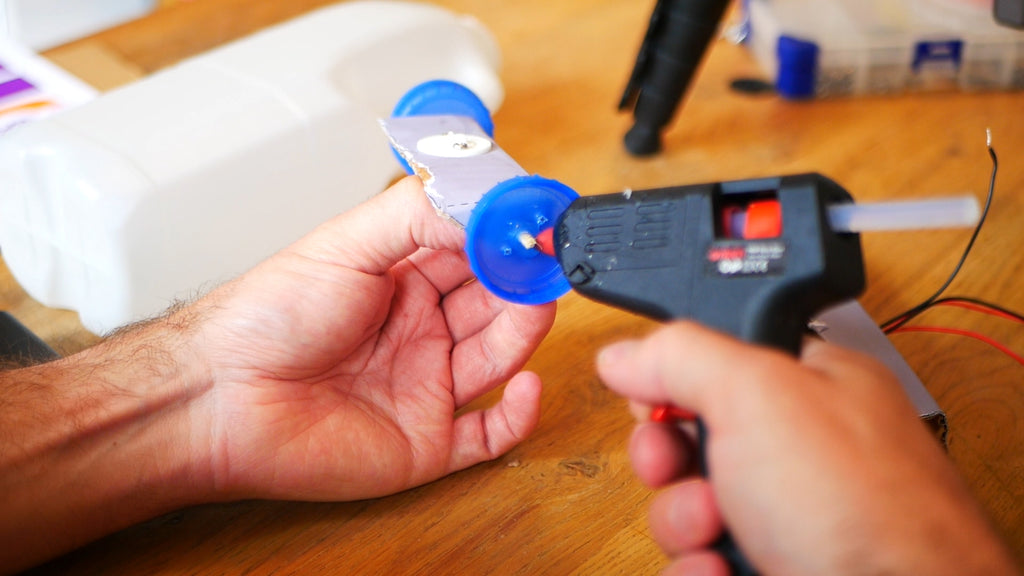 Image of a glue gun applying glue to a blue milk bottle lid