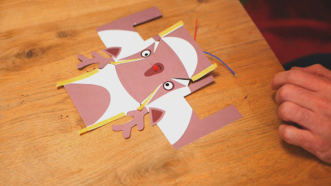 Image of a paper reindeer laying flat on a wooden table, with pieces of double sided tape stuck to it.