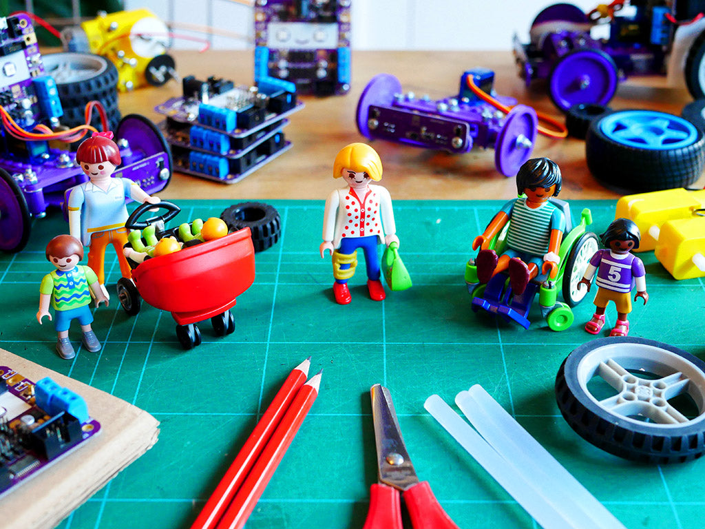 Photo of some Playmobil plastic figures, one of a woman with a buggy with two babies in and and a small child, one of a woman wearing a leg brace and one of a man using a wheelchair with a small child. They are standing on a cutting matt and surrounded by purple circuit boards, craft materials and tools and small wheels and motors.