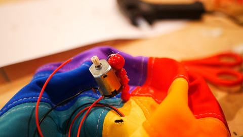Photo of small electric motor attached to a line of beads sticking out of the top of a multicoloured hat