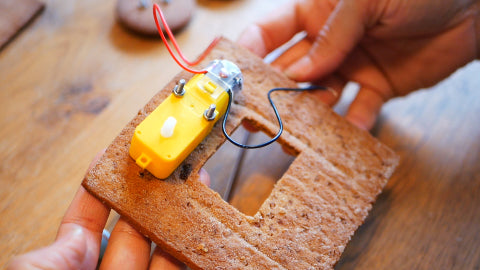 Image of a yellow motor screwed into a gingerbread side wall, that includes a small window.