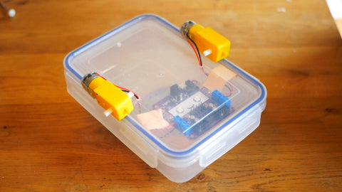 Image of a circuitboard attached to the inside of a Tupperware lid, along with two yellow motors attached to the lid of the container.