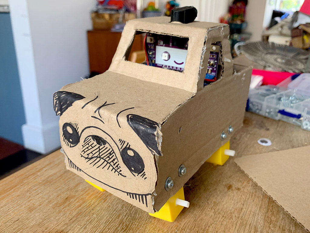 Photo of a cardboard monster truck with a purple smiling circuit board in the cab, four yellow gear motors and no wheels