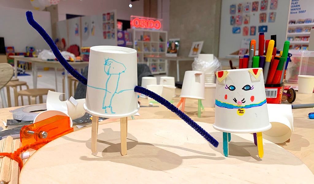 Two paper-cup based robots made by children, one with long blue pipe cleaner arms and a blue figure drawn on the front, the other decorated to look like a cat
