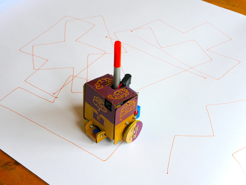 Image of a cardboard robot holding an orange pen, on a roll of white paper