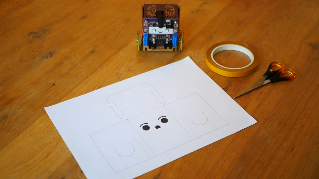 An image of a paper template, a pair of scissors, a roll of tape and a cardboard robot.