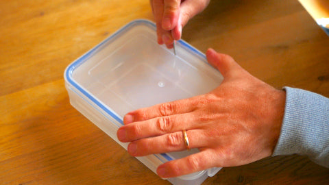 Image of someone poking a hole in a Tupperware container using a masonry nail.