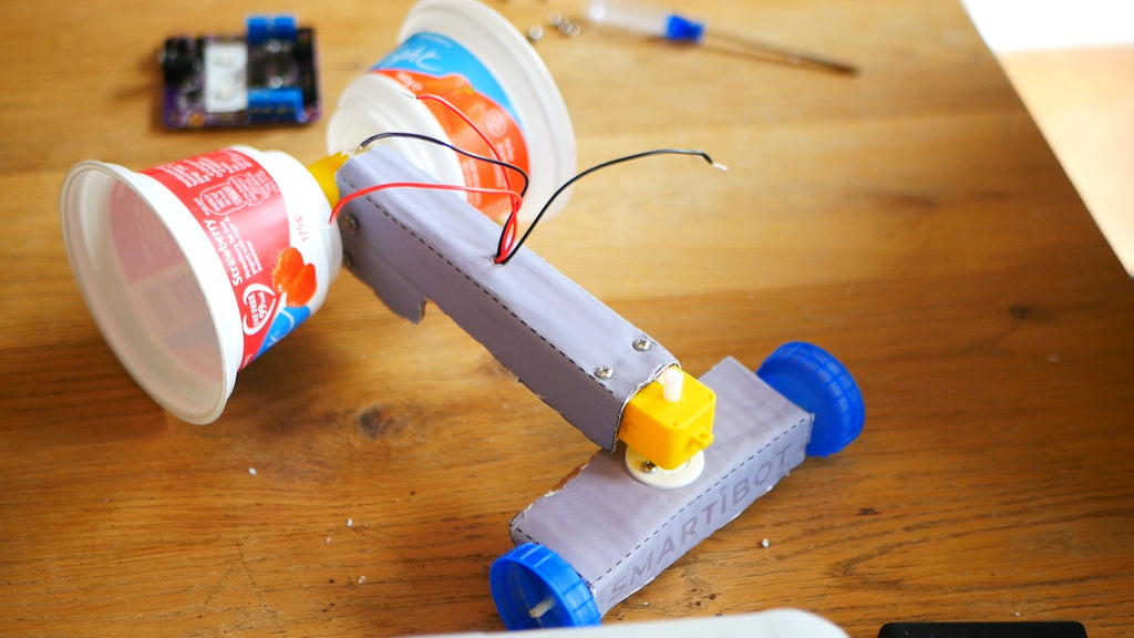 Image of a race car made from a cardboard axle and chassis, two yoghurt pots as rear wheels and two blue milk bottle lids as front wheels.
