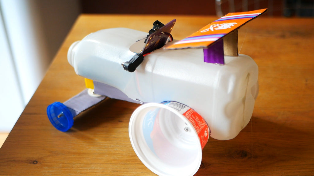 Image of the rear wing of a race car made out of a milk bottle, yoghurt pots as rear wheels and blue milk bottle lids as front wheels.