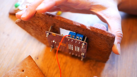Image of a circuit board attached to a piece of gingerbread house, and a red wire attached to the circuit board.