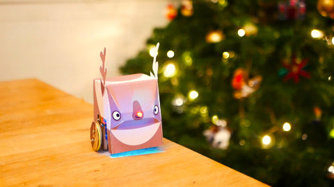 Image of a paper reindeer and a red light-up nose, with a Christmas tree in the background.