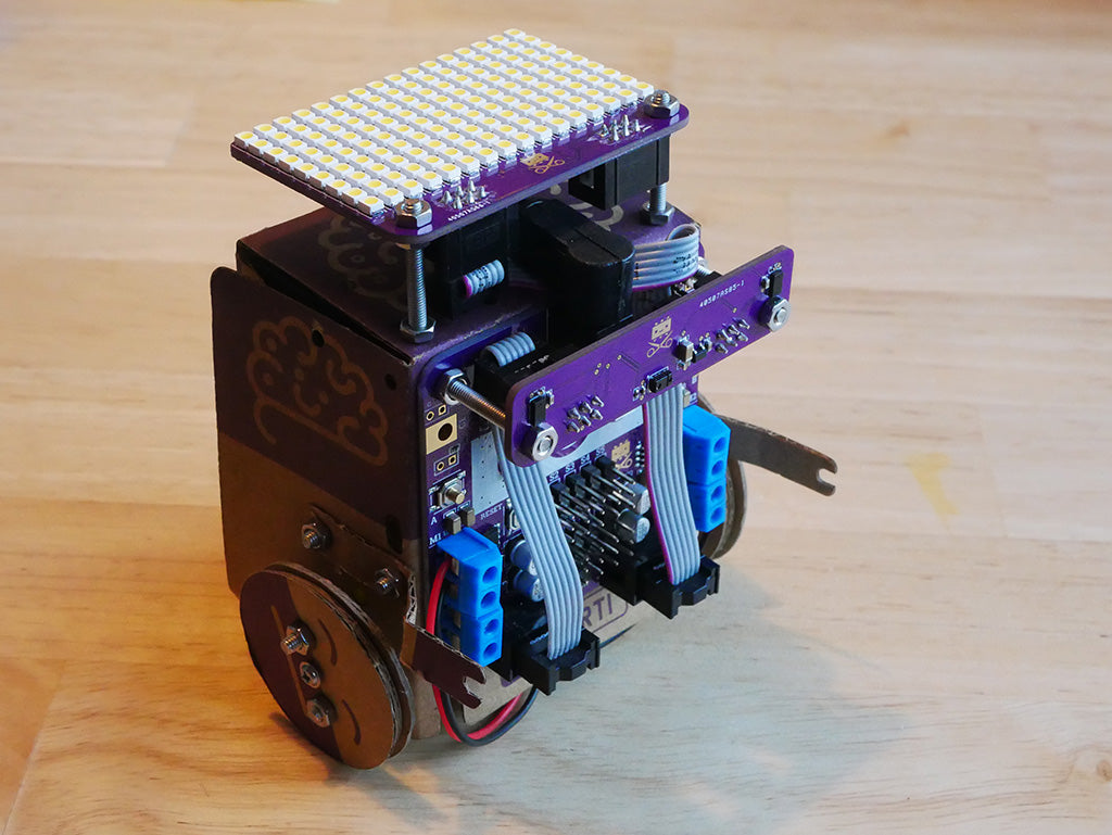 Photo of wheeled cardboard robot (Smartibot) with distance/gesture board mounted on the front and L.E.D. matrix on the rop