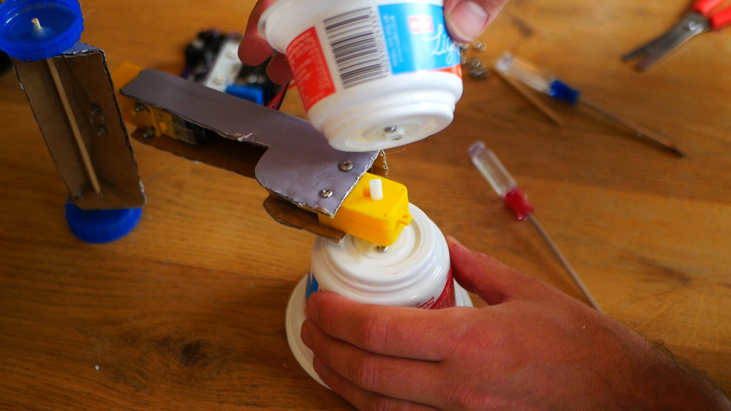 Image of a yoghurt pot being attached to a yellow motor that acts as an axle.
