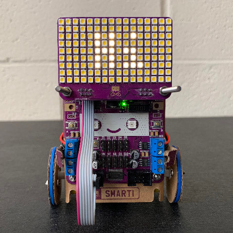 A small cardboard robot (Smartibot) with an LED matrix on the top displaying the text 'Hi'