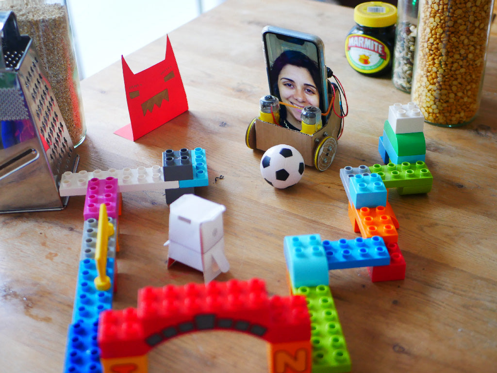 A wheeled cardboard robot containing a smartphone phone displaying a woman's face pushes a small football through a maze made from Duplo bricks, jars and a cheese grater