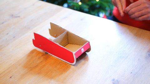 Image of a red sleigh made out of cardboard.