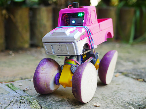 Photo of a pink toy monster truck with each wheel made out of half a turnip
