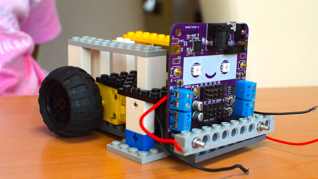 A picture of a half-done robot made out of LEGO bricks and a circuit board with a smiling face