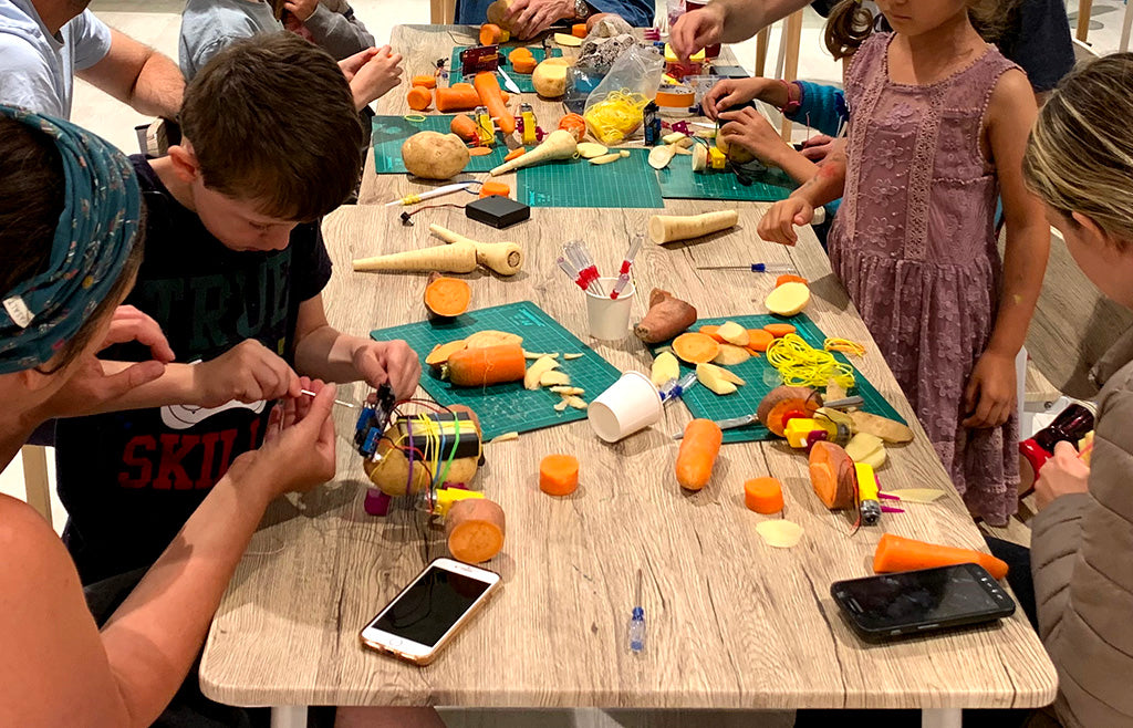 A table covered in pieces of vegetables, electronics and smartphones with children and adults intently working