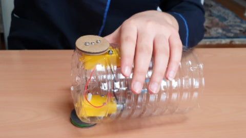 Image of half a plastic water bottle, with two yellow motors inside, and cardboard wheels attached to each motor