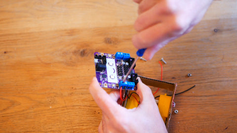 An image of a screwdriver screwing up a small blue chamber on a purple circuit board