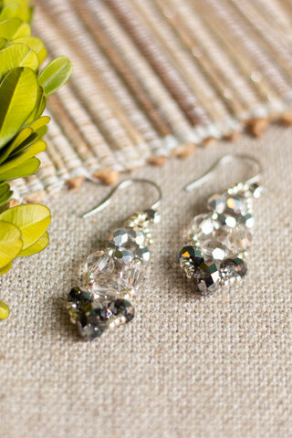 hand made beaded earrings in a chandelier drop style made from silver, gray and clear faceted beads with silver findings shown on linen background