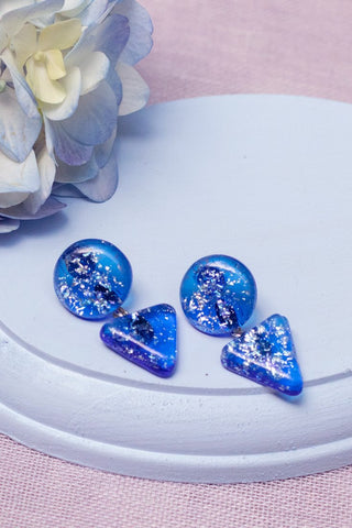 hand made fused glass drop earrings in blue with silver flecks with a round top and a triangle drop made by people with disabilities