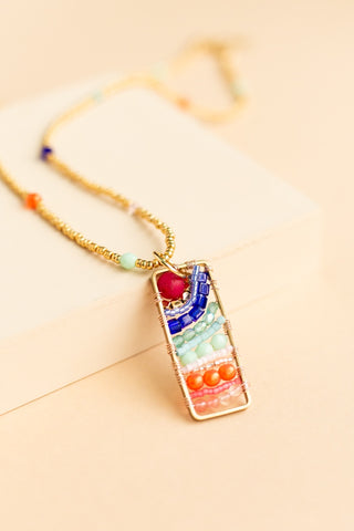 Naida multicolor beaded rectangular pendant with a radiating design and a beaded chain with gold beads and colored accent faceted beads