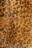 detail image animal print silk scarf in a caramel color with black animal print stamped on top at the ends made by people with disabilities
