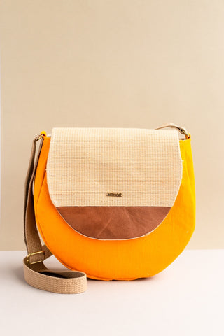 Tamarin Saddle bag in yellow handwoven by adults with disabilities with a crossbody strap and leather accent on front flap