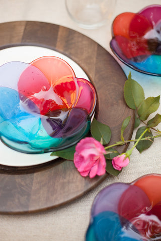 three fused glass bowls in a floral shape in shades of pink, peach, purple and blue hand made by people with disabilities