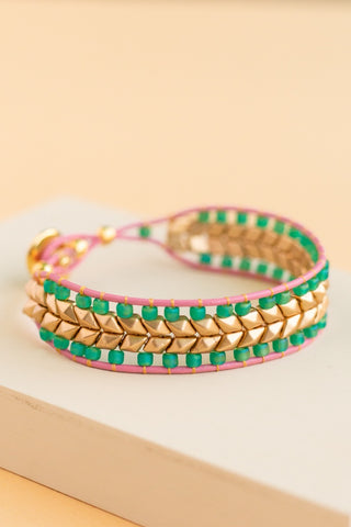Datana handmade beaded bracelet with pink edges and teal and gold beads in a chevron pattern with a teal and gold button closure made by people with disabilities