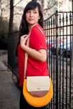 model wearing yellow, tan and leather tamarin bag over one shoulder