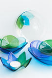 handmade fused glass tableware collection in shades of blue and green with a floral pattern handmade by people with disabilities