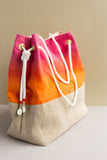 Side view of white strap tied on side of bucket bag hand woven and dyed by adults with disabilities with linen bottom band and a pink to orange ombre on top