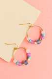 Hyacinth beaded hoop earrings with gold findings and symmetrical light pink, purple, blue, turquoise and gold beads handmade by people with disabilities