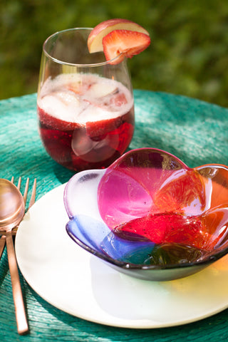 handmade Fused glass bowl in a floral shape in rainbow colors made by people with disabilities shown with a teal placemat and glass of wine