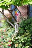 fused glass flower wind chime in rainbow colors hanging from tree