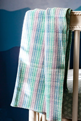 hand woven unisex baby blanket made from cotton and bamboo in stripes of green, blue, pink and white woven by people with disabilities