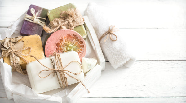 variety of bath soaps sitting on white table