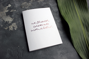 this hand foiled rose gold card is on white luxury paper with the phrase 'we should celebrate with alcohol'