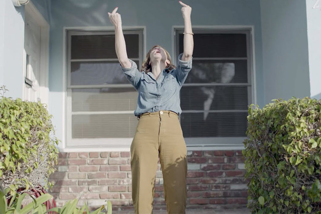 image of a female outside a house in a garden giving two middle fingers to teh sky