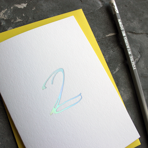 A second birthday card with a hand drawn number two hand pressed in holographic foil on the front