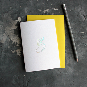 A fifth birthday card with a hand drawn number five hand pressed in holographic foil on the front and a yellow envelope